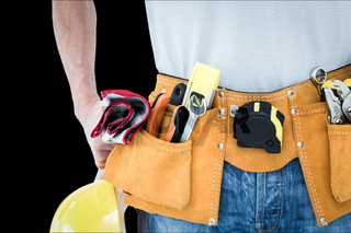 Composite image of technician with tool belt around waist