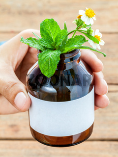 Doctor holding alternative health care fresh herbal in bottle with wooden background.