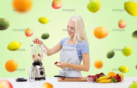 smiling woman with blender preparing shake
