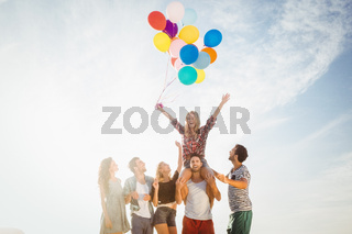 Portrait of friends holding balloon