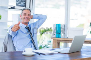 Happy businessman looking at camera with thumbs up
