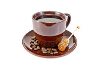 Coffee in brown cup with sugar and grains