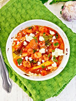 Shrimp and tomatoes with feta in white bowl on napkin top