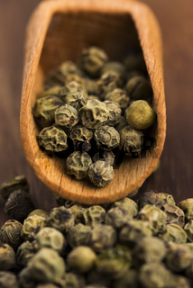 Green Peppercorns on wooden background