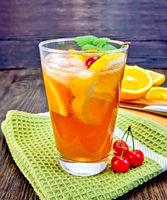 Lemonade with cherry in glassful on dark board