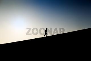 Silhouette of a man climbing a hill