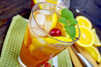 Lemonade with cherry in glassful on board
