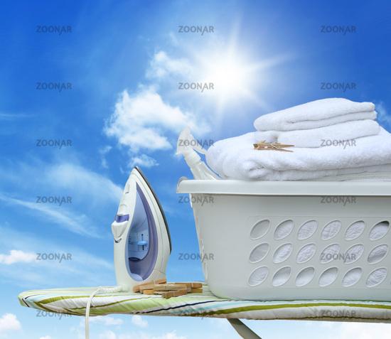 Iron on ironing board with basket