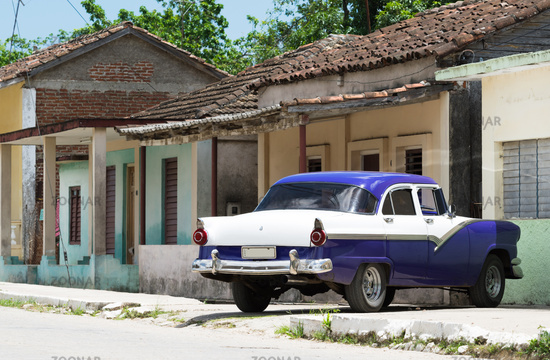HDR blue vintage car parked outside a house in the inland of Cuba