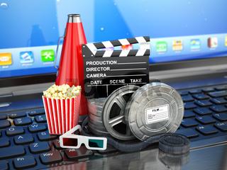 Video or movie online internet concept. Film reels, clapperboard and pop corn on laptop keyboard.