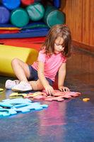 Mädchen löst Puzzle im Kindergarten