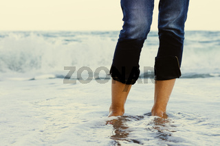 Female legs in jeans standing in the sea water on the background of a breaking wave