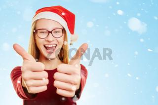 Frau im Schnee zu Weihnachten hält Daumen hoch