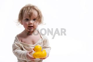 Kleinkind mit Gummiente und Strampelanzug