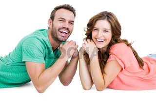 Happy young couple lying on floor looking at camera