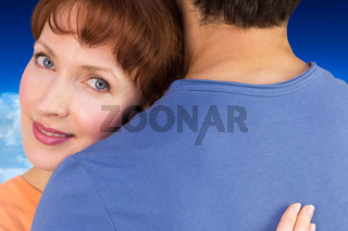 Composite image of happy couple hugging one another