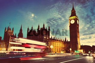 Red bus, Big Ben and Westminster Palace in London, the UK. at night. Moon shining. Vintage