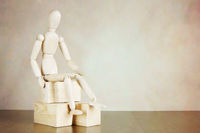 Wooden puppet sitting on the wooden blocks