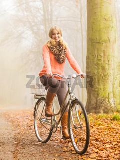 Active woman riding bike in autumn park.