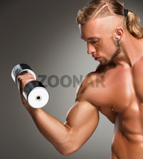 Closeup of a handsome power athletic man bodybuilder doing exercises with dumbbell