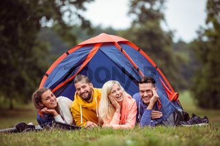 Happy friends lying in their tent
