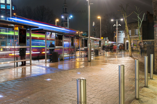 Bus stop, buses and commuters at night, Waterloo, London, UK