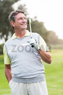 Golfer standing and swinging his club smiling at camera