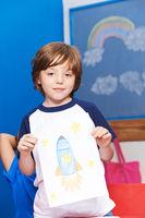 Kind zeigt Bild mit Rakete im Weltraum