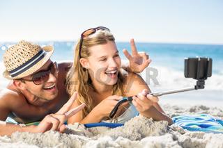 Happy couple taking selfie with selfie stick