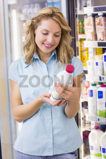 Smiling woman looking at a milk bottle