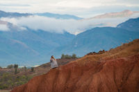 Woman sitting on big red sandstone rock formation slope in hot dry desert of Tatacoa, Huila