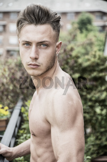 Handsome shirtless muscular young man outdoor