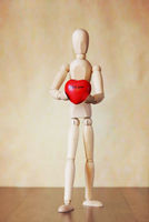 Wooden puppet holding a red heart in its hands. Conceptual image about love confession