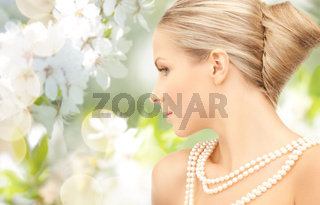 woman with pearl necklace over cherry blossom