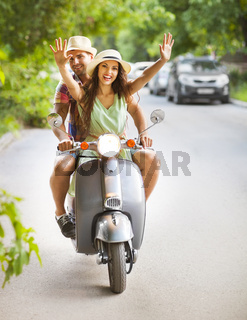 Happy young family riding a vintage scooter in the street wearing hats