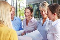 Viele Geschäftsleute reden draußen miteinander