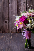 Pink bouquet from gillyflowers and alstroemeria on old, rustic wooden background