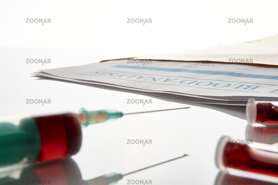 Syringe and vials with blood on glass table and report
