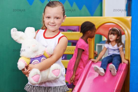 Mädchen mit Kuscheltier im Kindergarten