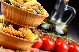 Raw eliche and penne tricolori pasta in the wooden bowls