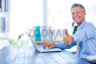 Happy businessman using laptop computer and looking at camera with thumbs up