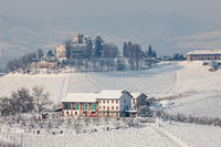 Rural house on snowy hills in Italy.