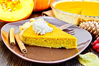 Pie pumpkin in brown plate with cream on board