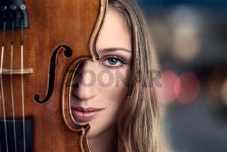 Junge Frau hält ihre Geige vors Gesicht
