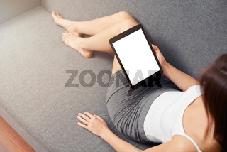 Woman takes a rest with tablet, on sofa