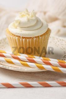 Closeup of vanilla cupcake with straws