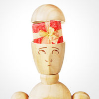 Gift box into the human head. Abstract image with a wooden puppet
