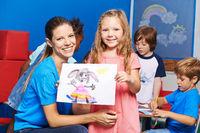 Mädchen zeigt gemaltes Bild im Kindergarten