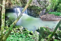 Small waterfall in a stone cave with moss rocks