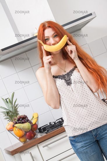 Happy Woman Holding Banana Dancing in the Kitchen